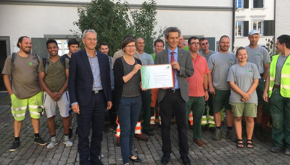 Stadtpräsident, Baureferentin und Bereichsleiter Grün nehmen zusammen mit Mitarbeitenden von Grün Schaffhausen das Label Silber entgegen.